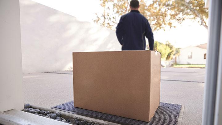 Paketbote stellt Paket an der Haustür ab